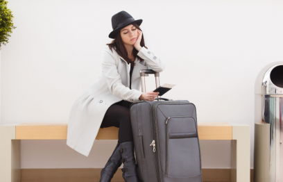 A tired woman sitting, looking at phone with a suitcase beside her.