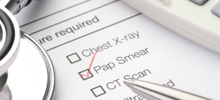 Doctors check list of tests required with a red tick next to Pap Smear